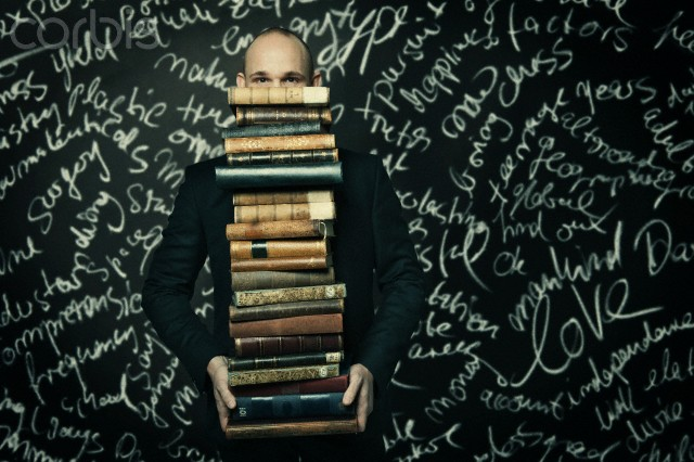 Man carrying large stack of books